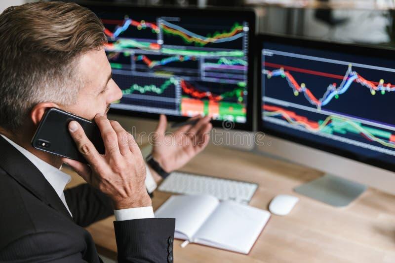 可爱的商人画象发表演讲关于手机,当工作与在计算机上的数字图表在办公室时 免版税库存图片