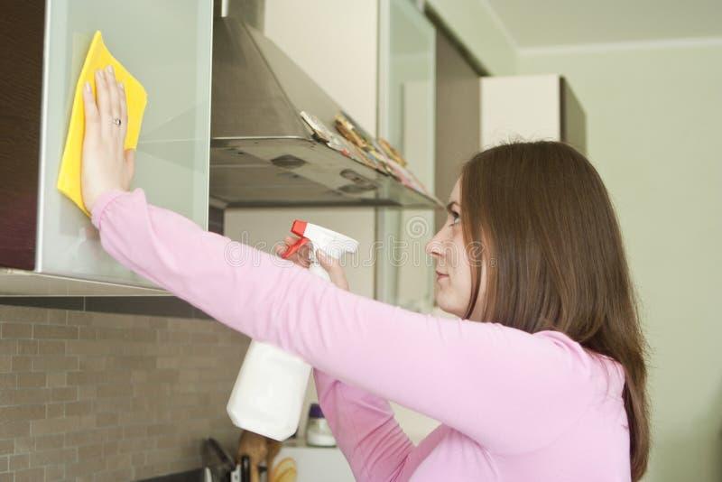 可爱的在厨房的女孩擦亮的家具 库存照片