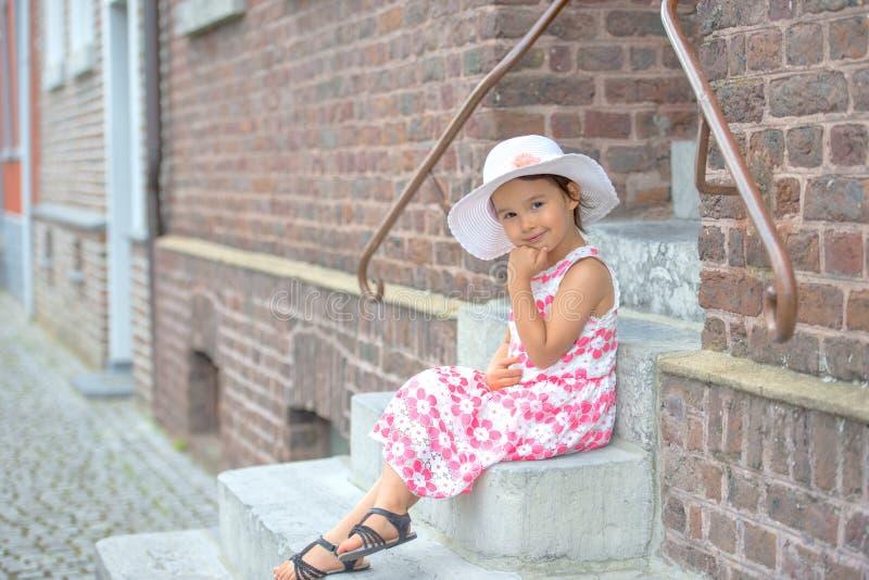 可爱的在台阶的女孩佩带的白色帽子开会 免版税库存图片
