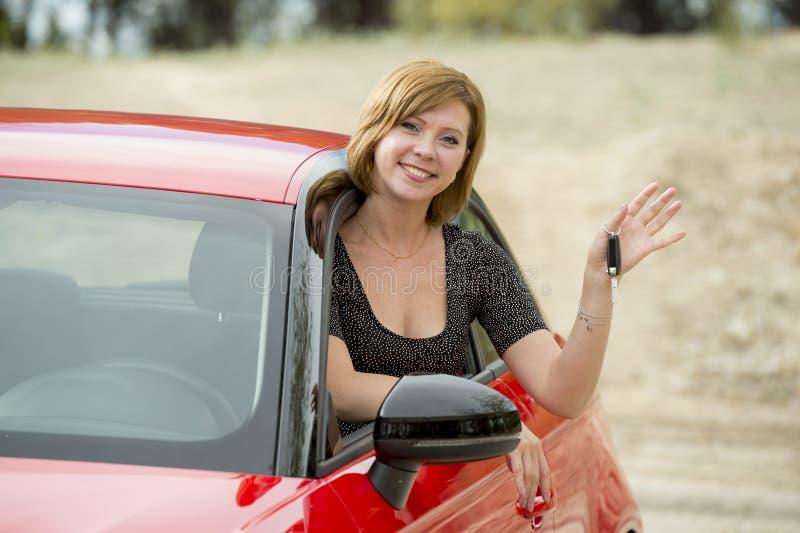可爱的在把握和显示汽车关键的驾驶席的妇女微笑的骄傲的开会在新汽车购买和租赁 库存照片