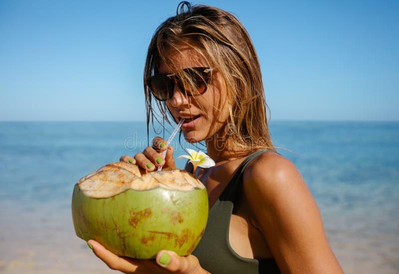 可爱的在海滩的妇女饮用的椰子水 库存照片