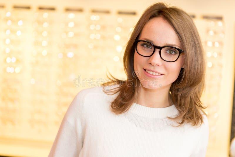 年轻可爱的在眼镜师的妇女尝试的玻璃 免版税库存照片