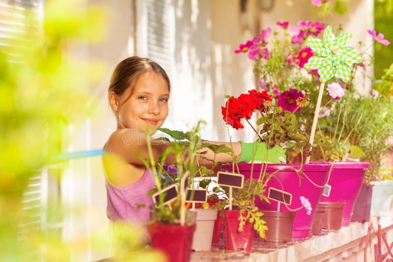 可爱的在阳台的女孩装壶红色大竺葵 免版税库存图片