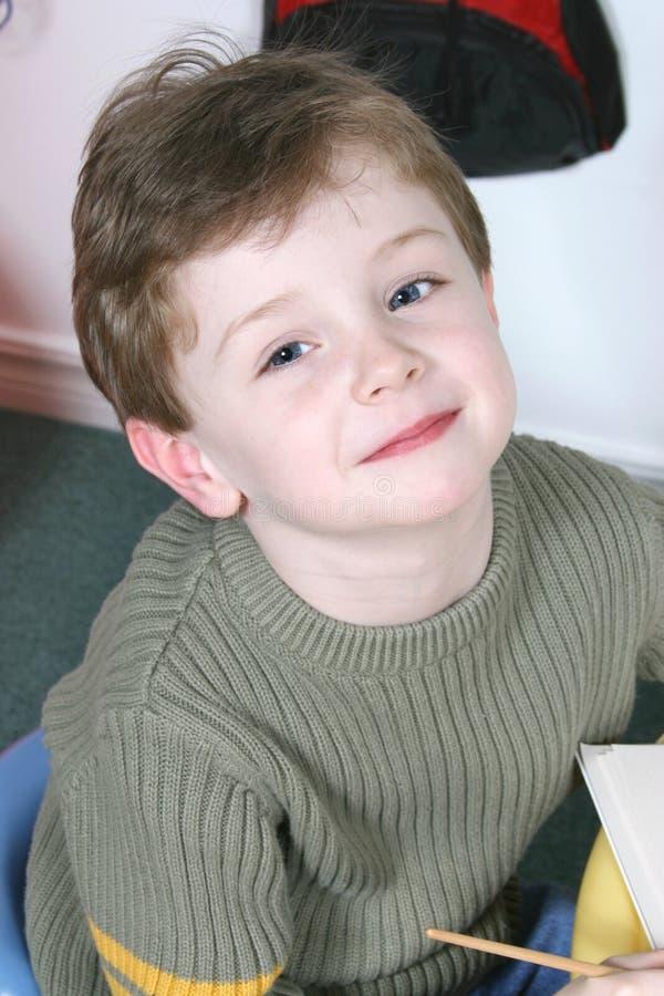 可爱的大穿蓝衣的男孩注视四老年 免版税库存照片