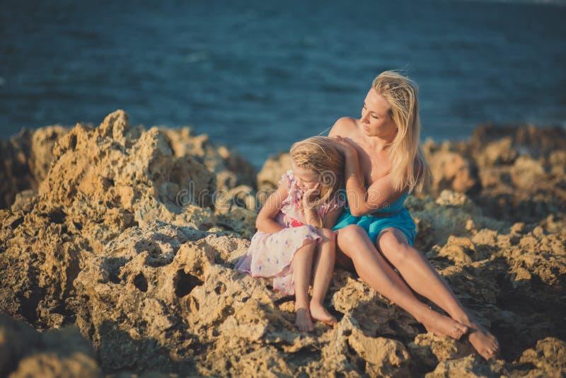 可爱的夫人母亲坐岩石在浅兰的礼服靠岸与她佩带桃红色通风dre的逗人喜爱的矮小的白肤金发的女儿一起 库存图片
