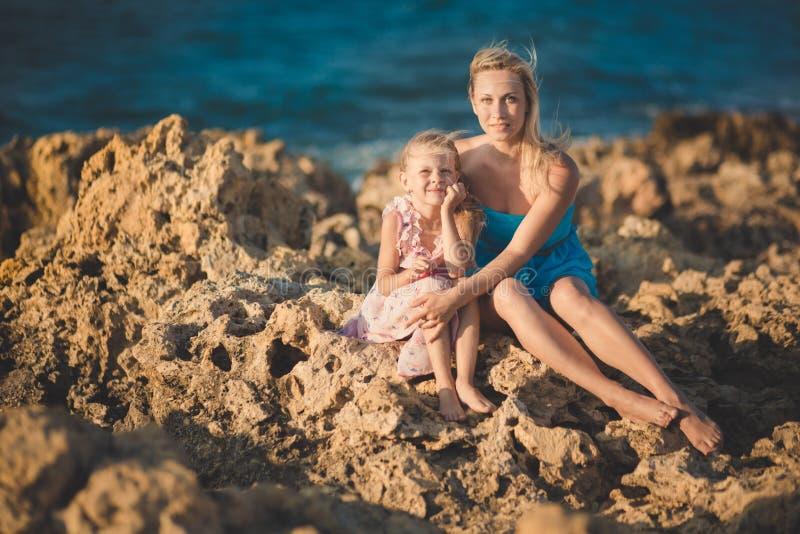 可爱的夫人母亲坐岩石在浅兰的礼服靠岸与她佩带桃红色通风dre的逗人喜爱的矮小的白肤金发的女儿一起 免版税库存照片