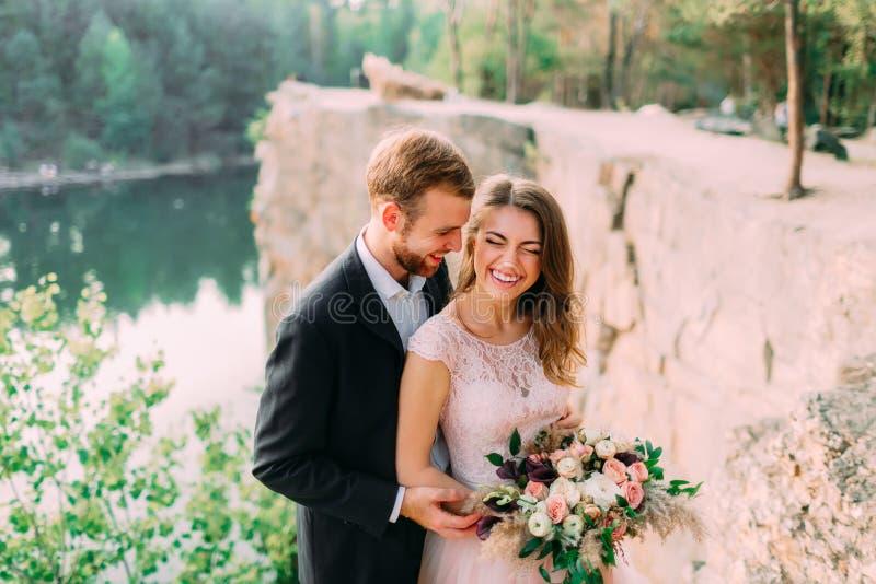 可爱的夫妇新婚佳偶新娘和新郎笑并且微笑,愉快和快乐的片刻 婚姻的仪式户外 免版税库存图片