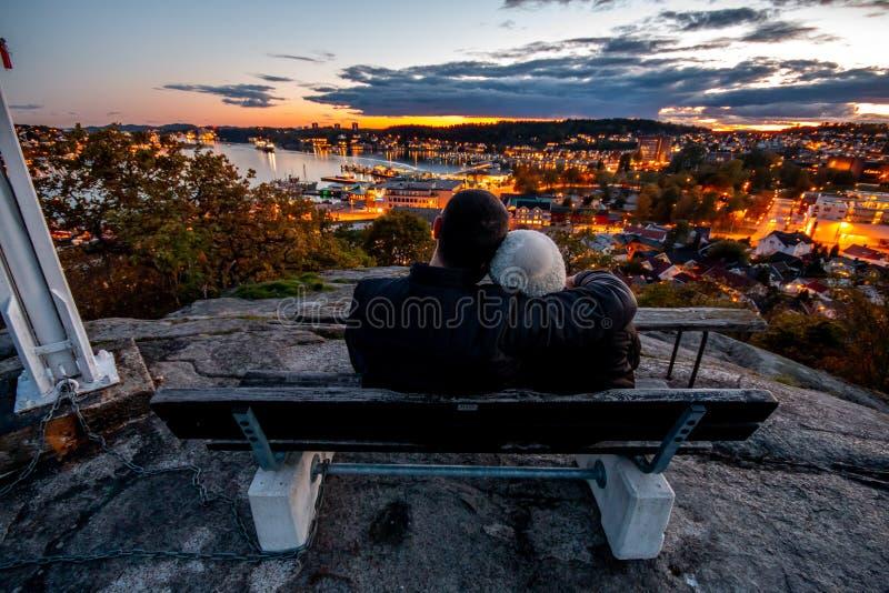 可爱的夫妇观看的日落在桑德尔福德西福尔郡挪威 库存照片
