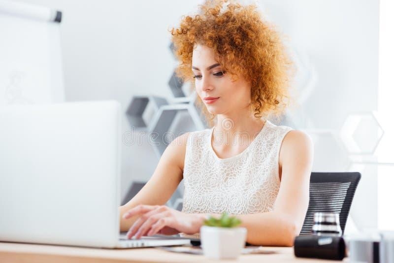 可爱的女商人与膝上型计算机一起使用在办公室 免版税库存图片