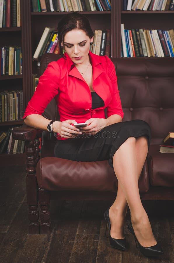 可爱的女商人在办公室给坐皮革穿衣 免版税库存照片