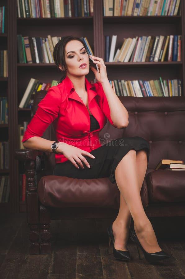 可爱的女商人在办公室给坐皮革穿衣 库存图片