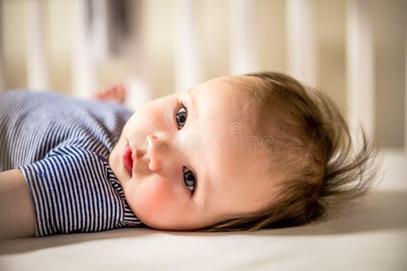 可爱的女婴在小儿床放置 库存照片