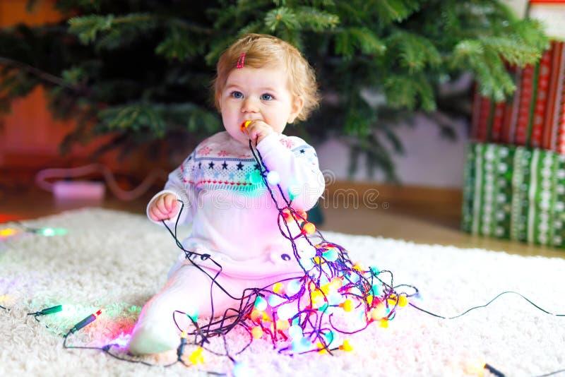 可爱的女婴在逗人喜爱的手上的拿着五颜六色的光诗歌选 欢乐衣裳的小孩装饰圣诞节的 免版税库存照片