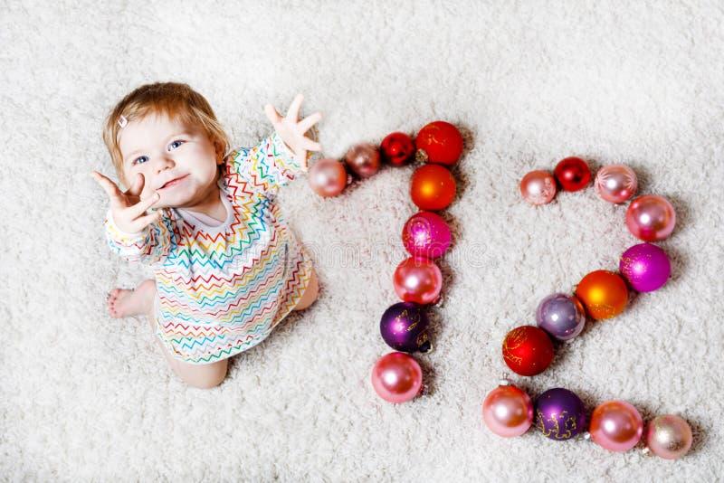 可爱的女婴在逗人喜爱的手上的拿着五颜六色的葡萄酒xmas玩具球 作为十二的小孩和圣诞树球 免版税库存照片