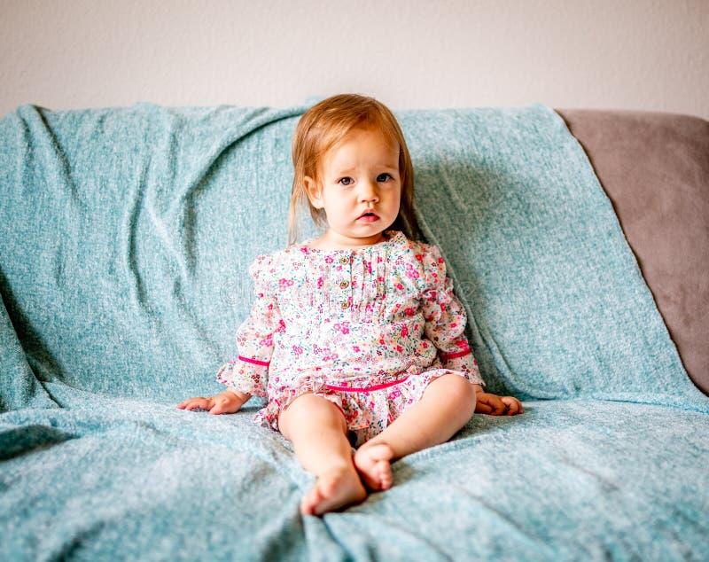 可爱的女婴坐长沙发 免版税库存图片