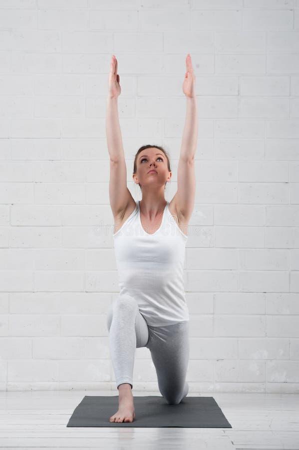 年轻可爱的女子实践的瑜伽户内 免版税库存图片