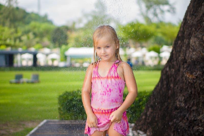可爱的女孩作为阵雨在热带海滩胜地的树下 免版税库存照片