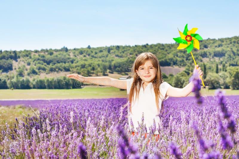 可爱的女孩使用与在淡紫色领域的轮转焰火 免版税图库摄影