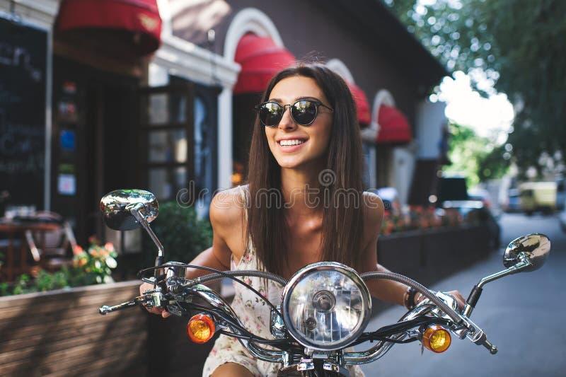 年轻可爱的女孩和葡萄酒老滑行车 免版税库存照片