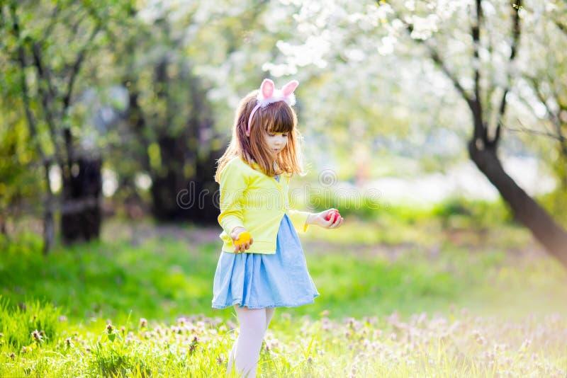 可爱的女孩在使用在庭院里的绿草坐复活节彩蛋狩猎 库存照片