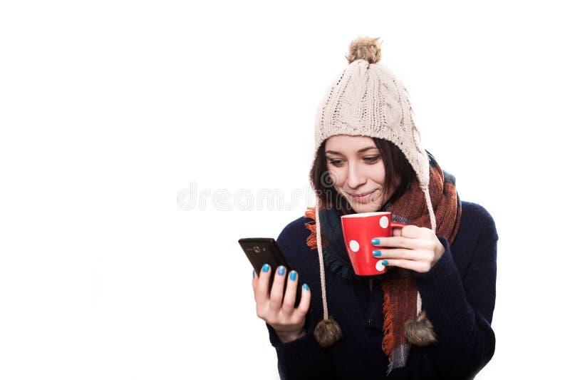 可爱的女孩在冬天嗅到她热的汤,当佩带一件欢乐色的羊毛衫时 库存照片
