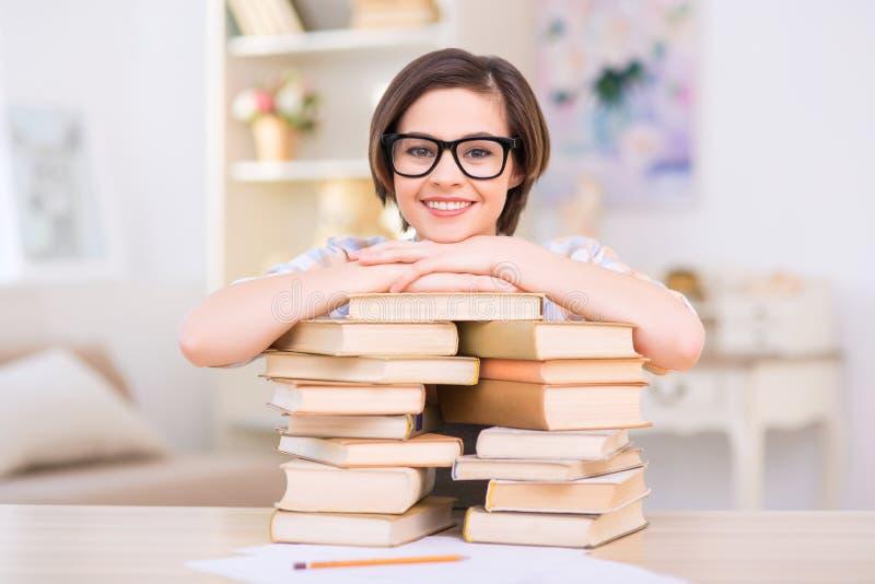 年轻可爱的女孩在堆倾斜书 图库摄影