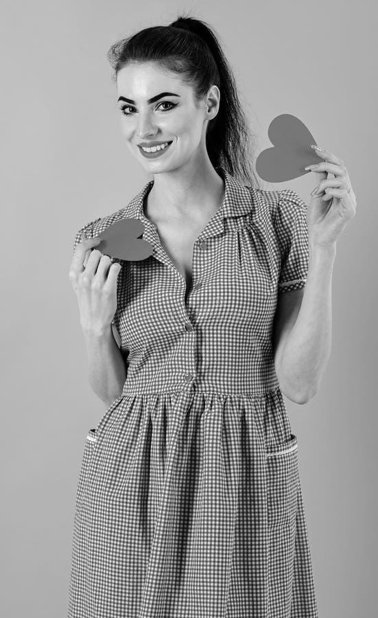 可爱的女孩在她的手上的拿着两红色心脏,隔绝在桃红色背景 爱,愉快,华伦泰概念 免版税库存照片