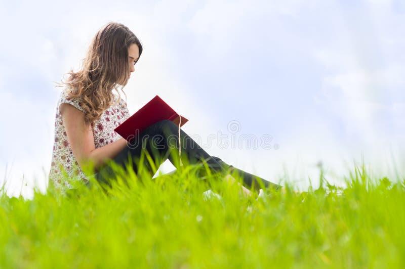 可爱的女孩在她的日志和坐写户外 免版税库存照片