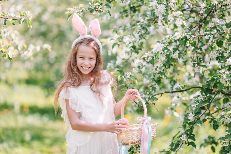 可爱的女孩在开花的苹果庭院里在美好的春日 免版税库存图片