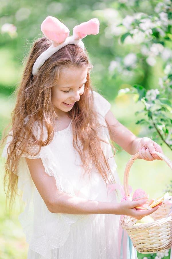 可爱的女孩在开花的苹果庭院里在美好的春日 免版税库存照片