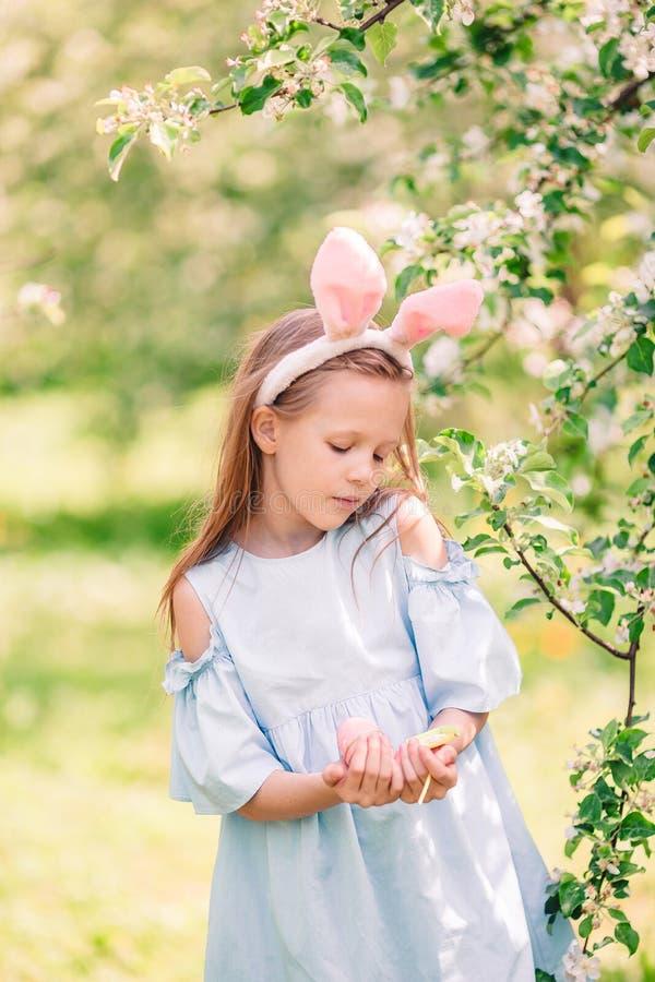 可爱的女孩在开花的苹果庭院里在美好的春日 库存图片