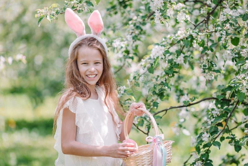 可爱的女孩在开花的苹果庭院里在美好的春日 免版税图库摄影