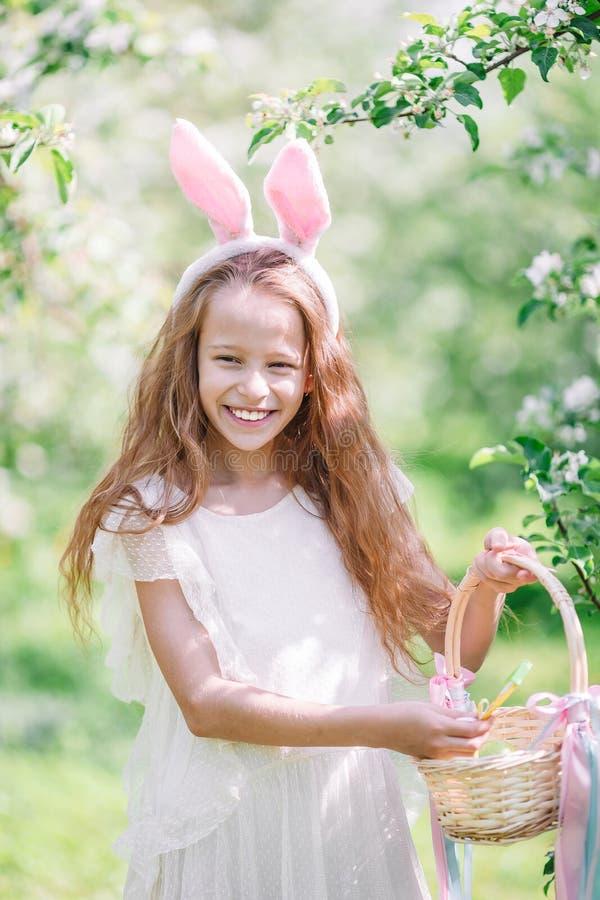 可爱的女孩在开花的苹果庭院里在美好的春日 库存照片
