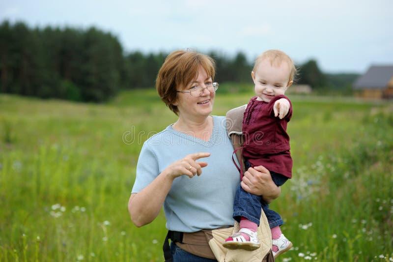 可爱的女孩在有祖母的一个草甸 库存图片