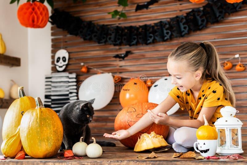 可爱的女孩坐哺养她猫南瓜籽的桌 万圣夜生活方式背景 免版税库存照片