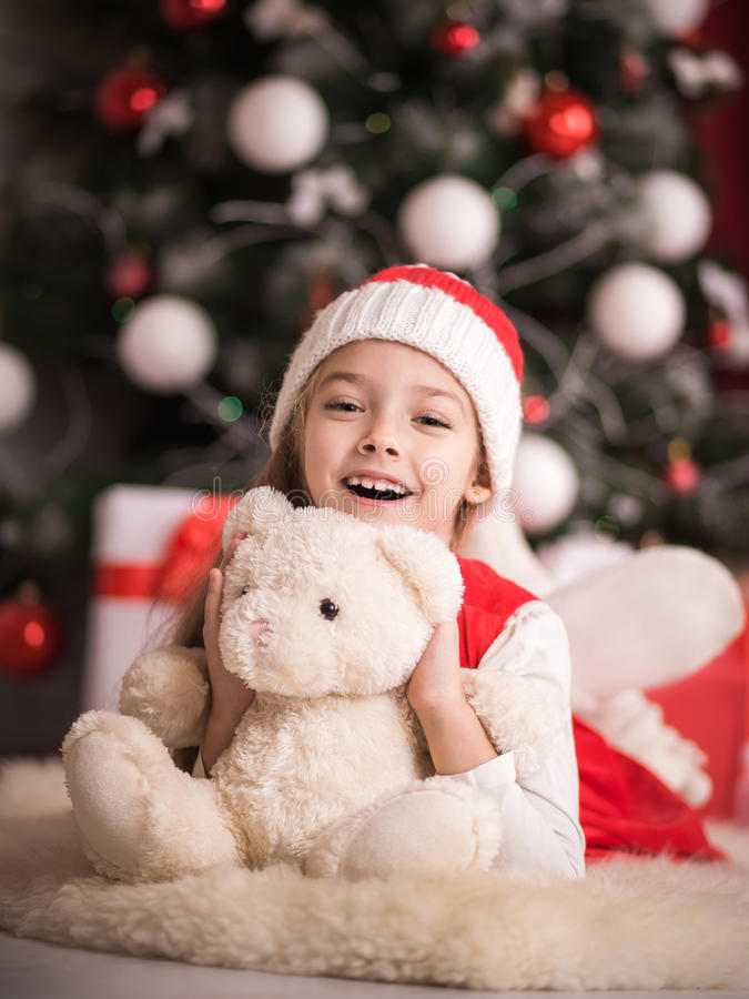 可爱的女孩坐地板在与熊的圣诞树附近,演播室射击,定调子在葡萄酒样式 免版税库存照片