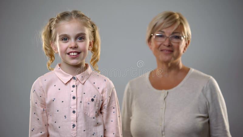 可爱的女孩微笑对照相机的,站立资深的夫人后边,支持 免版税库存照片
