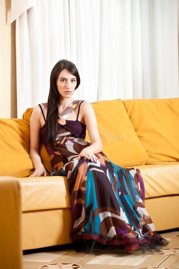 可爱的女孩性感的坐的微笑的沙发 免版税图库摄影