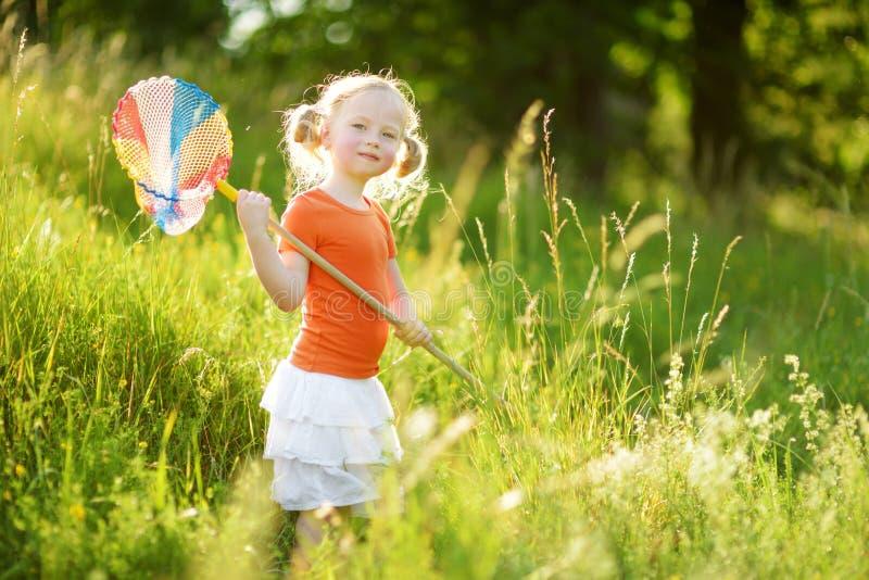 可爱的女孩捉住的蝴蝶和臭虫与她的瓢网 儿童探索的自然在晴朗的夏日 库存照片