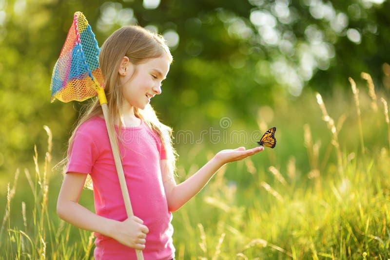 可爱的女孩捉住的蝴蝶和臭虫与她的瓢网 儿童探索的自然在晴朗的夏日 库存图片