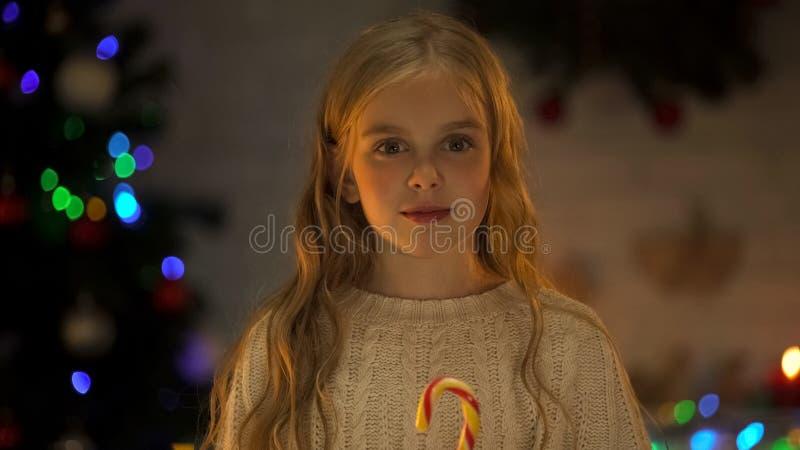 可爱的女孩用看照相机,等待的圣诞老人圣诞节奇迹的糖果 免版税库存图片