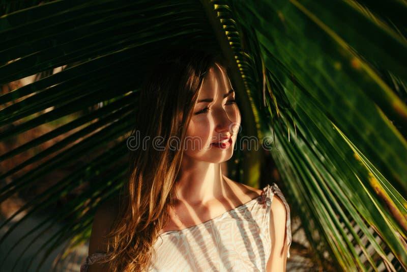 可爱的女孩画象在大绿色棕榈下的 免版税库存图片