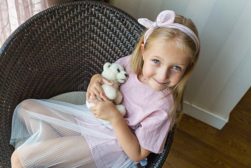 可爱的女孩画象有被充塞的玩具熊的在摆在为摄影的手上,当坐椅子时 免版税库存照片