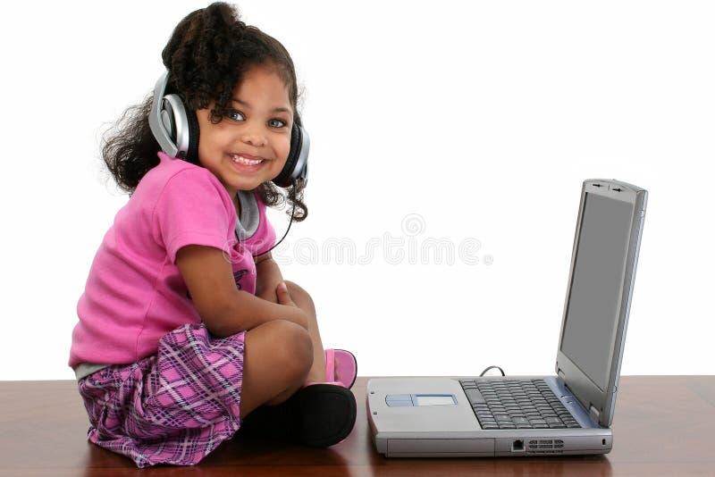 可爱的女孩耳机膝上型计算机 图库摄影