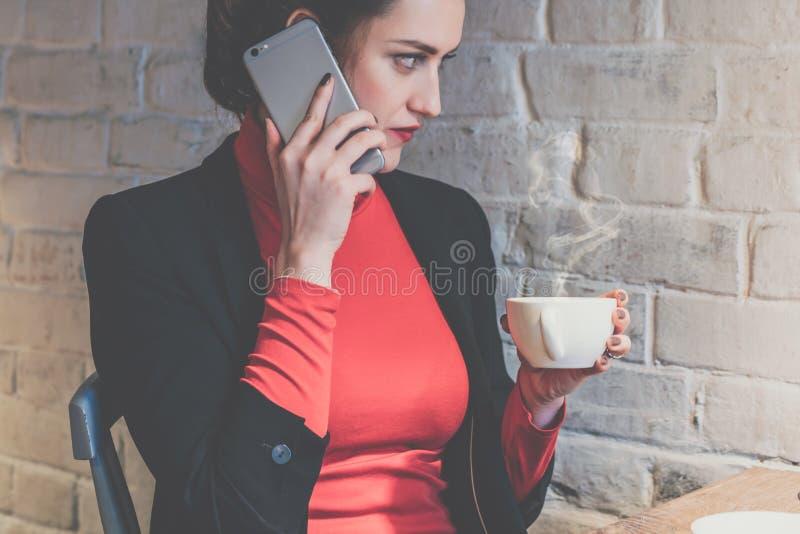 年轻可爱的女实业家坐在咖啡馆在桌,饮用的咖啡上和谈话在手机 免版税库存照片