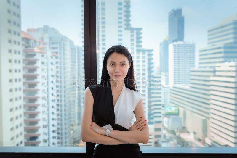 可爱的女实业家画象站立与横渡的胳膊摆在在办公楼俯视的Windows前面 图库摄影