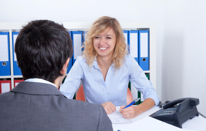 可爱的女实业家讲话与客户 免版税图库摄影