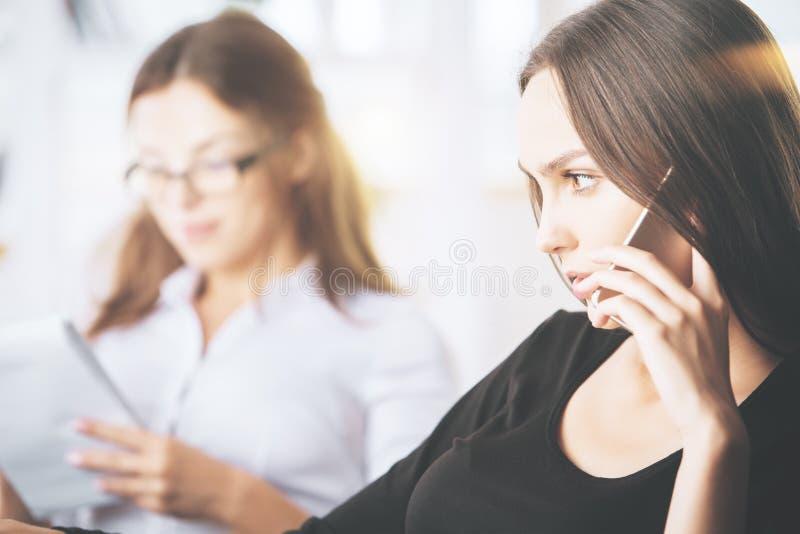 可爱的女实业家谈话在电话 免版税库存照片