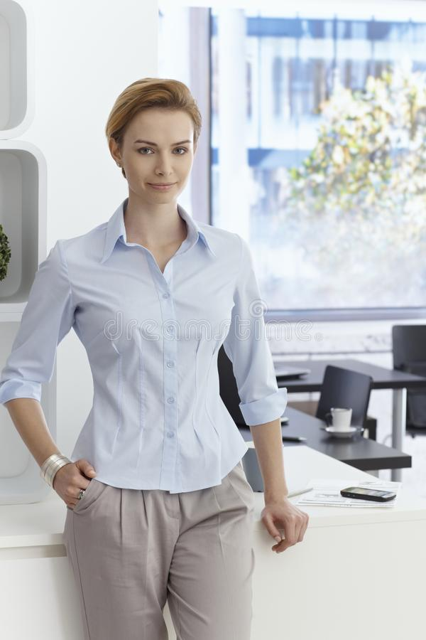 可爱的女实业家画象在办公室 免版税库存图片