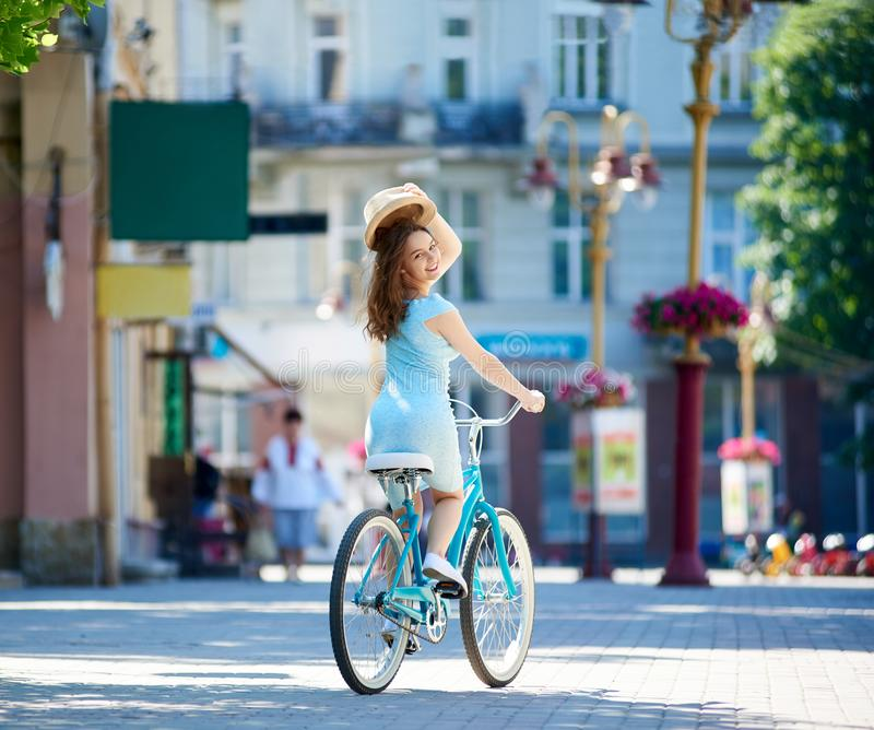 可爱的女性在市中心拿着她的帽子当问候标志,当骑蓝色自行车在晴朗的夏日期间时 免版税库存图片